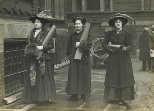 three Suffragettes preparing to chain themselves to railings in 1909.
