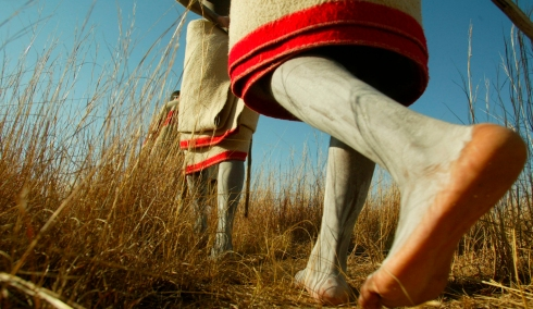 Initiates walk bare footed as part of tradition in the field outside an initiation school in the Eastern Cape